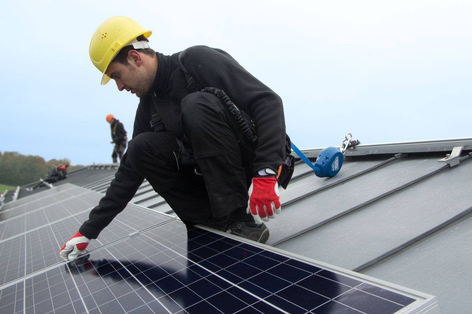 Worker using rail system for working at height to cleaning solar panel