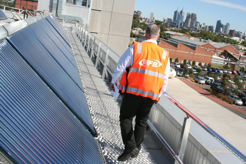 Worker using roof walkway used to gain access to solar panels close to edge of building for maintenance