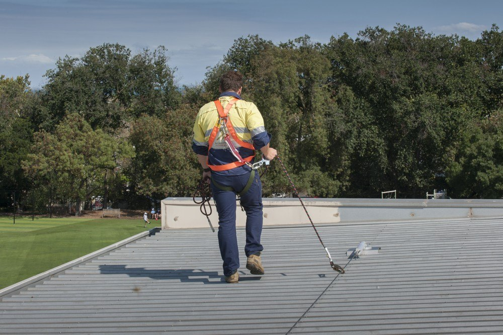 working on roof, using static line to gain roof access to gutters
